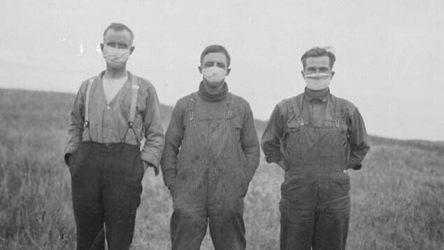 Photo en noir et blanc montrant trois hommes dans portant chacun un masque en tissu.