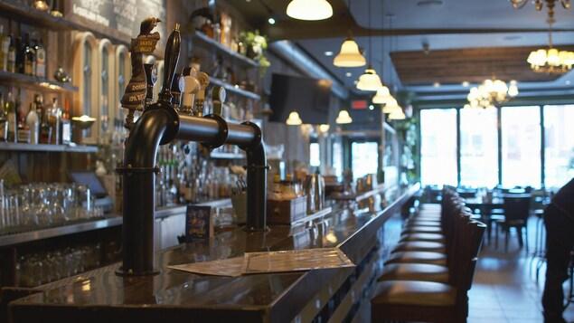 L'intérieur d'un restaurant-bar vide. La photo montre le long comptoir du bar et la rangée de chaise en attente de clients.
