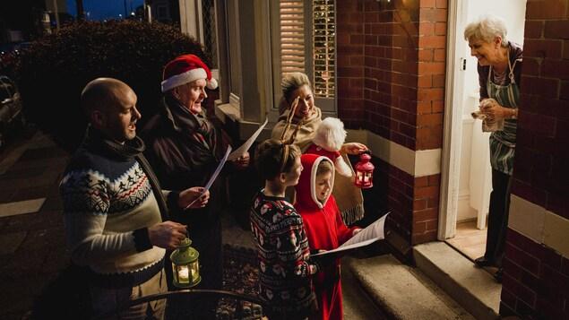 Trois générations d'une famille chantent à la porte d'une maison.