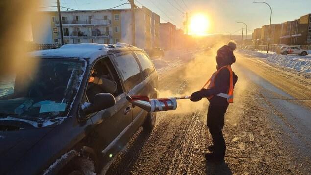 Une bénévole recueille des sous auprès d'un automobiliste pour la Guignolée de 2020.