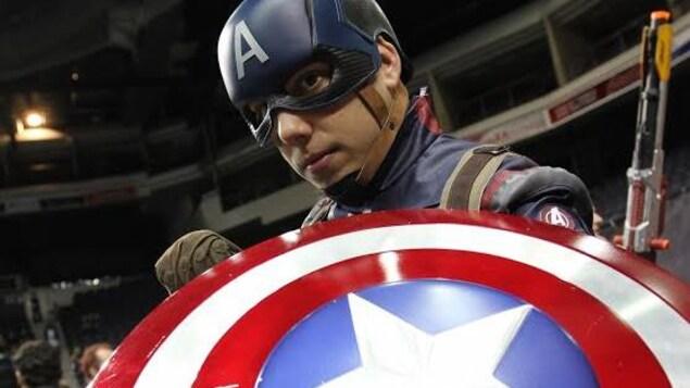Un homme casqué exhibe le bouclier de Captain America.