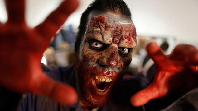 Gros plan sur un humain déguisé en monstre. Le visage en question est couvert de faux sang.