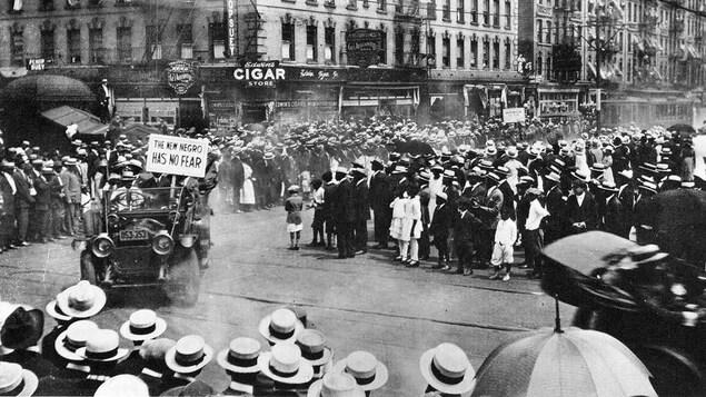 Une foule de plusieurs centaines de personnes réunies au coin d'une rue au début des années 1920.