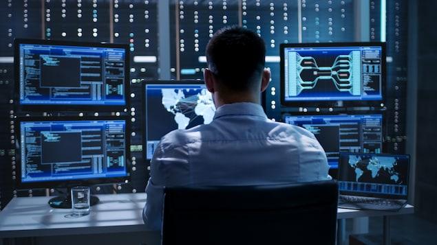 Un homme devant plusieurs écrans d'ordinateur.