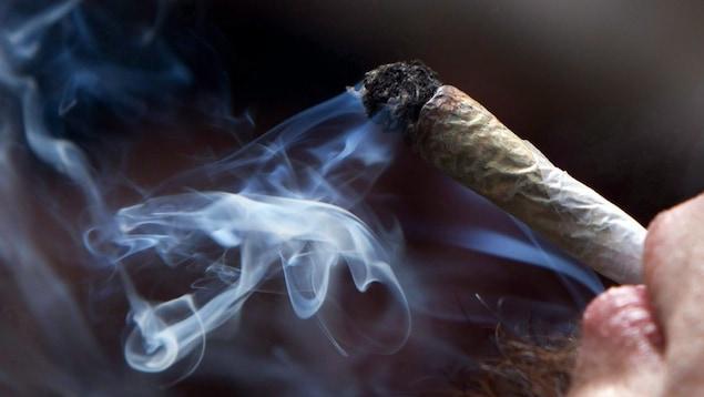 Un jeune homme fume du cannabis.