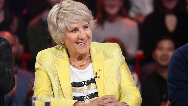 Elle porte  un veston jaune.