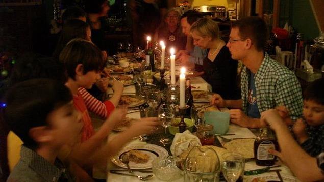 Dix, douze personne sont attablées à une  table rectangulaire à côté du sapin de Noël ornée de quatre chandelles.