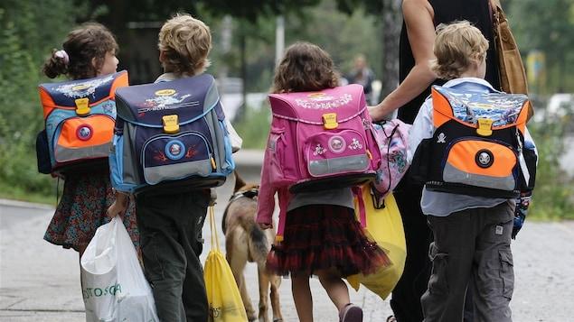 Quatre jeunes enfants, cartables sur le dos, marchent accompagnés d'un adulte.