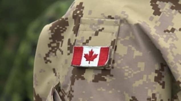 Plan serré d'un drapeau sur l'épaule d'un uniforme des Forces armées canadiennes