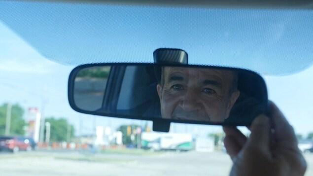 Le reflet d'un homme dans un miroir d'auto.