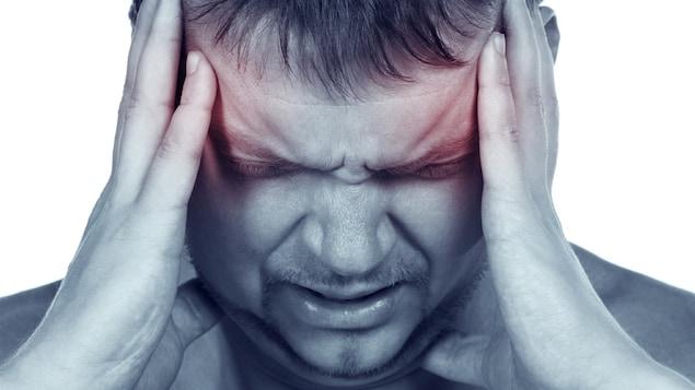 Un homme se serre la tête entre deux mains. Il souffre de douleur. Il a un mal de tête.