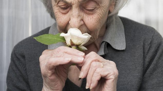 Une femme sent une rose.