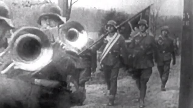 Des soldats allemands avec trompettes et drapeaux avancent sur un chemin vers la Pologne.