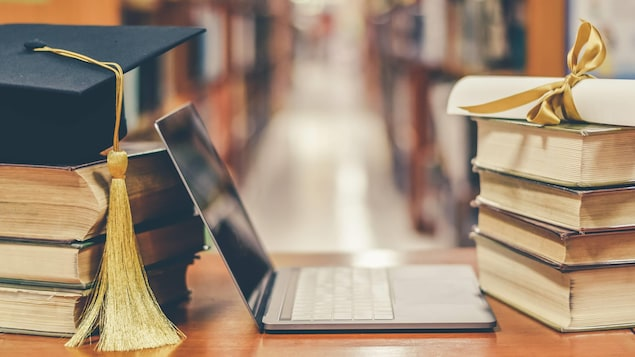 Un mortier, un ordinateur portable, un diplôme et des livres posés sur une table dans une bibliothèque.