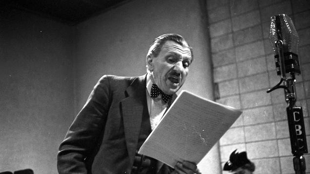 Photo en noir et blanc montrant un homme en train de réciter un texte dans un micro.