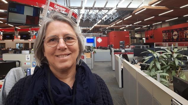 Une femme est posée dans une salle de nouvelle