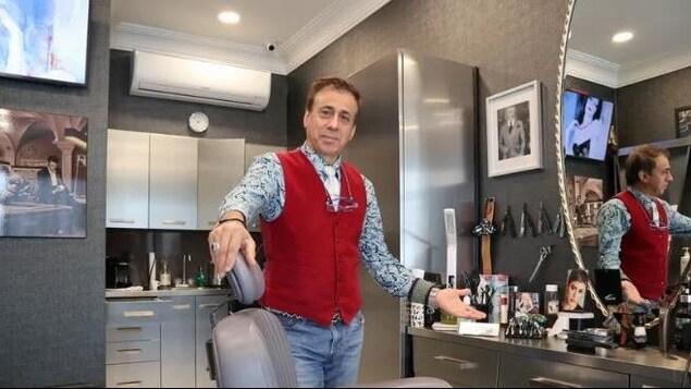 Un homme debout près d'un comptoir de salon de coiffure.