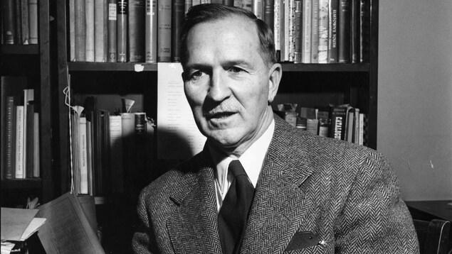 Le sociologue américain Everett Hughes parle devant une bibliothèque.