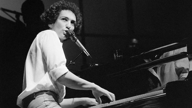 Michel Berger chante en jouant du piano pendant un concert.