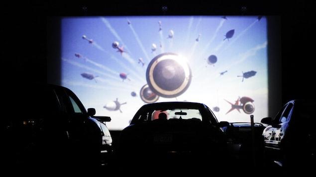 Une personne regarde un film dans sa voiture dans un ciné-parc.