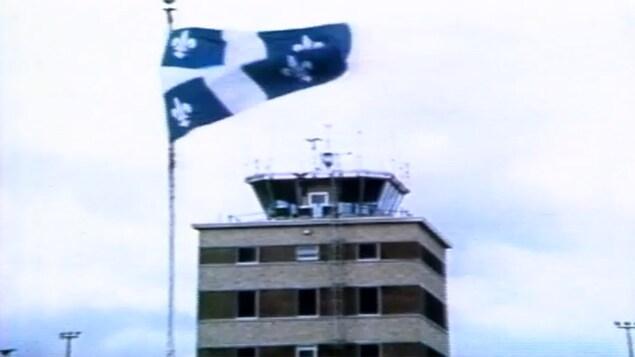 Drapeau québécois devant un centre de contrôle aérien.