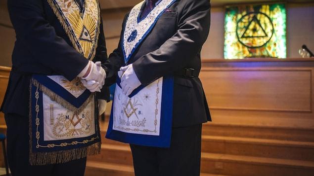 Deux francs-maçons en costume échangent une poignée de main devant un vitrail à l'effigie maçonnique.