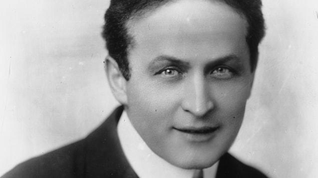 L'illusionniste Harry Houdini, en complet cravate, regarde la caméra.
