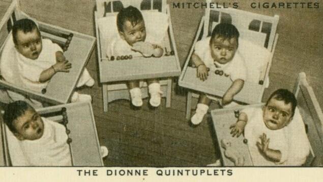 Les jumelles Dionne dans des chaises hautes.