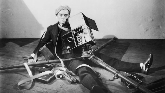 Buster Keaton, par terre sous une caméra, vêtu d'un béret, sur une photo promotionnelle pour le film Le contrôleur, en 1928.