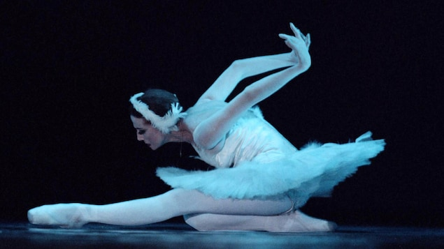 Une ballerine en costume exécute un mouvement sur le sol sur une scène.