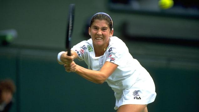 Une joueuse de tennis serre les dents avant de frapper avec sa raquette une balle qui arrive.