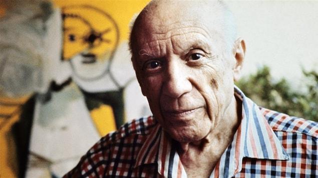 Picasso en chemise devant l'un de ses tableaux.