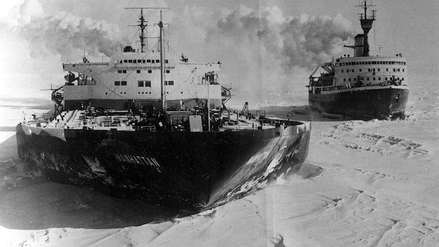 Photo en noir et blanc de deux navires naviguant dans la glace.