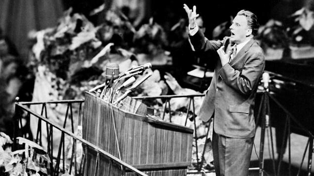 Un homme debout sur une tribune parle devant un pupitre et plusieurs microphones.