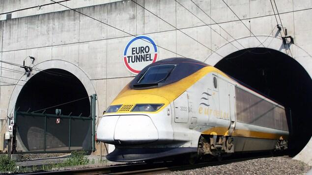 Un train jaune et blanc nommé Eurostar sort d'un tunnel qui porte le nom d'Eurotunnel.