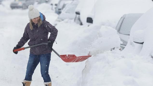 Une femme pellette la neige pour libérer sa voiture dans les rues de Montréal.