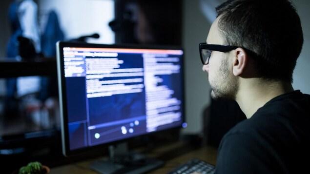 Un homme à lunettes est devant un ordinateur.