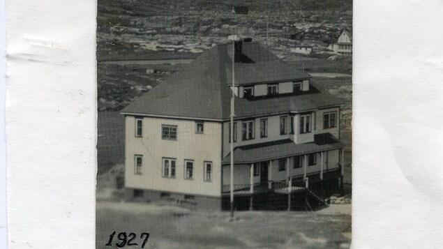 Une photo d'archives en noir et blanc présente une importante bâtisse construite dans une lande.