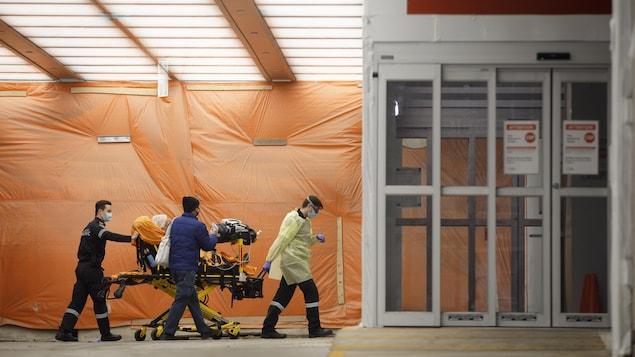 Des ambulanciers transportent un patient sur une civière à l'urgence d'un hôpital.