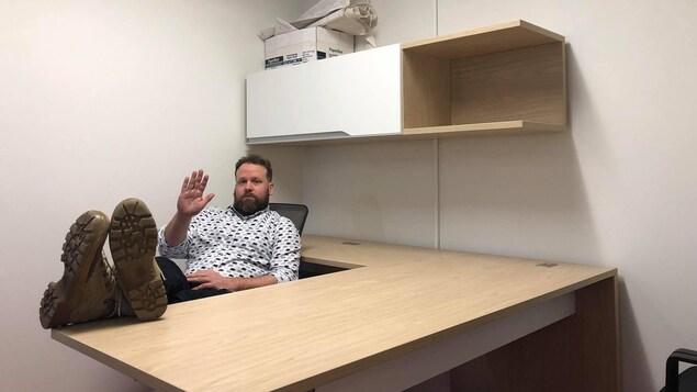 Hugo Meunier pose dans un bureau vide en faisant un signe d'au revoir de la main.