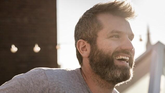 Un homme regardant vers la droite, souriant, devant un paysage urbain.