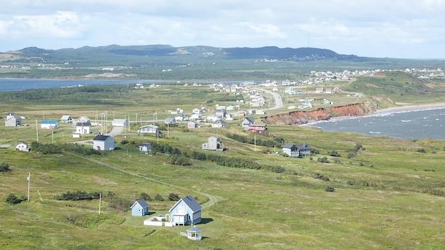 Vue sur des maisons et la mer, avec les collines de Bassin à l'arrière