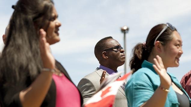 Des immigrants lors d'une assermentation pour l'obtention de la citoyenneté canadienne.