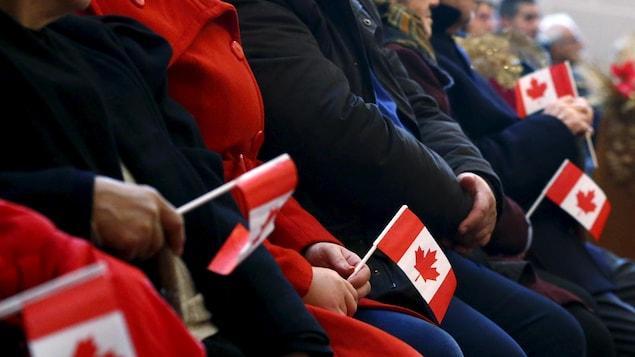Des personnes dont on ne voit pas le visage sont assises et tiennent dans leurs mains un petit drapeau canadien.