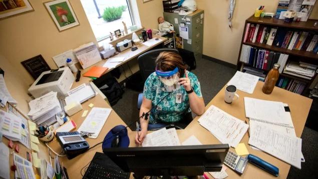 Une employée responsable du traçage de contacts dans son bureau.