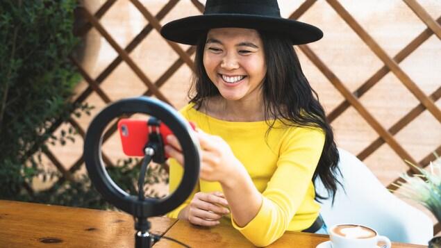 Une jeune femme sourit vers son téléphone, assise à une table sur laquelle se trouve un cercle lumineux, et un café.