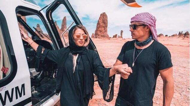 Une femme et un homme près d'un hélicoptère