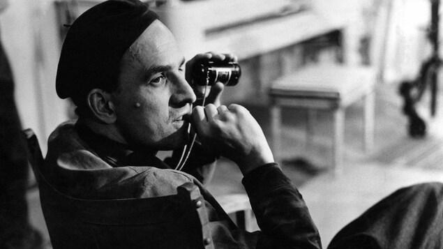 Un cinéaste est assis sur sa chaise avec une lunette optique dans la main gauche.