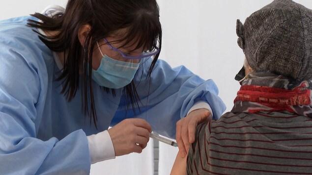 Une femme vaccine une aînée.