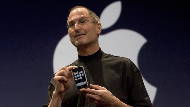 L'homme tient dans ses mains un petit téléphone pour le montrer au public.